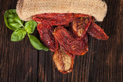 Sundried tomatoes on wooden table. Royalty Free Stock Photo
