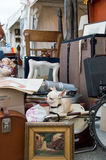 Sundries. Small antiques market. on an old chair, a dog relaxes in the middle of the old or ancient objects Stock Photos