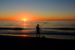 Sunest fishing ocean. Sunset on the Gulf Of Mexico beach golden ball with a few clouds over the ocean. Blue ocean and golden red sky with man as a silhouette Stock Image