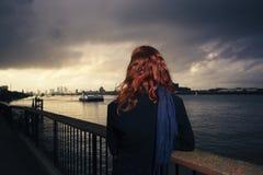 Sunet admiratif de femme au-dessus de rivière dans la ville Image stock