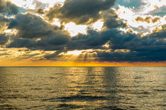 Sunflare through the clowds at the sea Royalty Free Stock Photography