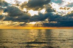 Sunflare przez clowds przy morzem Fotografia Royalty Free