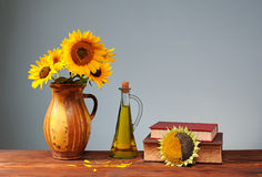 Sunflower in a ceramic vase, oil and books Royalty Free Stock Photo
