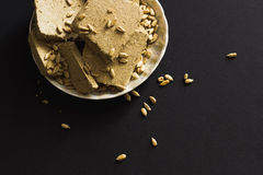 Sunflower halva with seeds on plate, on black background Royalty Free Stock Photos