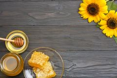 Sunflower with honey, Honeycomb and honey dipper on dark wooden table. Top view with copy space Stock Images