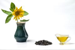 Sunflower oil in a glass gravy boat, a bunch of sunflower seeds and a sunflower with a fly in a vase. Isolated on the white backgr Royalty Free Stock Photo