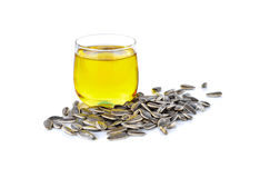 Sunflower oil in glass and sunflower seeds on white Royalty Free Stock Photos
