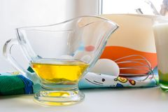 Sunflower oil in a glass transparent oiler on a white windowsill next to the ingredients for pancakes. Close up stock images