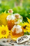 Sunflower oil with seeds. Closeup photo of sunflower oil with seeds on wooden background in the garden royalty free stock image