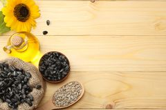 Sunflower oil, seeds and flower on light wooden background. top view with copy space Stock Photography