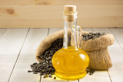 Sunflower oil and seeds on wood Royalty Free Stock Images