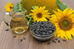 Sunflower, oil and seeds on a wooden background. Royalty Free Stock Photo