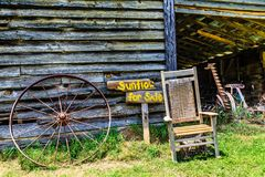 Sunflower for Sale. A sign Sunflower for Sale by an old Chair and old rustic barn and rusty wheel Stock Photography