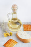 Sunflower seed oil in the glass jug, cookies, slice bread and fl Stock Photography