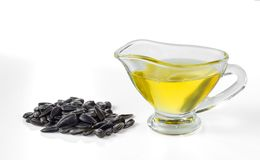 Sunflower seed oil and a handful of sunflower seeds. Sunflower seed oil in a glass gravy boat and a handful of sunflower seeds isolated on a white background stock image