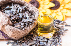 Sunflower seed. S in the sack and sunflower oil in a glass on wooden background Royalty Free Stock Photo