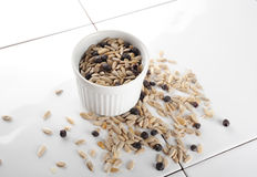 Sunflower Seeds. And raisins in a small white cup and scattered on a ceramic table stock photography