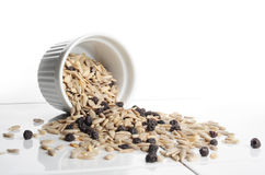 Sunflower Seeds. And raisins in a small white cup and scattered on a ceramic table royalty free stock image
