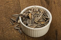 Sunflower seeds. In the bowl over the wooden background royalty free stock image
