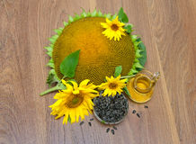 Sunflower seeds, flowers and oil on a wooden background. Royalty Free Stock Image