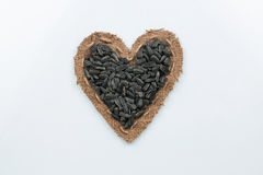 Sunflower seeds  lies at the heart made of burlap Royalty Free Stock Photo