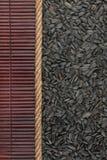Sunflower seeds  lying on dark bamboo mat, for menu Royalty Free Stock Photos