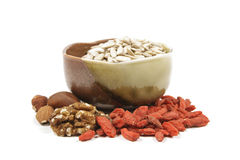 Sunflower seeds with nuts and goji berries. Sunflower seeds in a brown and green bowl with mixed nuts and goji berries on a reflective white background royalty free stock image