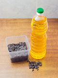 Sunflower seeds in plastic tray and bottle of sunflower oil Royalty Free Stock Image