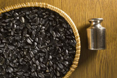 Sunflower seeds and plummet. Sunflower seeds in a wicker basket and plummet on a wooden background Stock Photography
