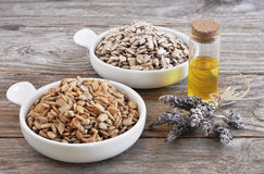 Sunflower seeds raw and roasted with a bottle of sunflower oil. Royalty Free Stock Photo