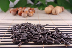 Sunflower seeds on a striped bamboo napkin. Seeds of sunflower and nuts on a striped bamboo napkin removed close up Stock Photos