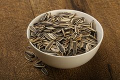 Sunflower seeds. In the bowl over the wooden background Royalty Free Stock Photography