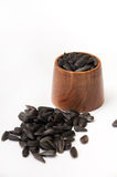 Sunflower seeds on a white background and in a wooden glass Royalty Free Stock Images
