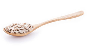 Sunflower seeds in wooden spoon on white background. Sunflower seeds in wooden spoon isolated on white background Stock Photography