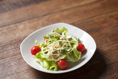 Sunflower sprout salad with small tomato. On white dish Royalty Free Stock Images