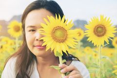 Sunflower and a woman hiding behind it. Selective focus at woman`s eye Stock Images