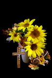Sunflowers of Faith. Vase of sunflowers with cross, autumn leaves and room for copy space royalty free stock image