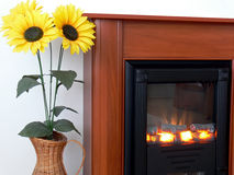 Sunflowers at fireplace. Sunflowers in a vase standing next to a modern fireplace Royalty Free Stock Image