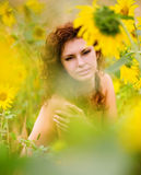 Sunflowers and the girl. The girl with curly hair sits in sunflowers Stock Photos