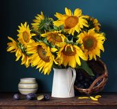 Sunflowers and plums. Still life with flowers and berries. stock photo