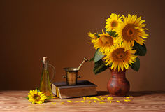 Sunflowers in a vase, books and oil in a bottle Royalty Free Stock Images