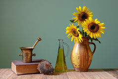 Sunflowers in a vase, oil and books Stock Image