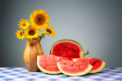 Sunflowers in a vase and sliced watermelon Royalty Free Stock Photo