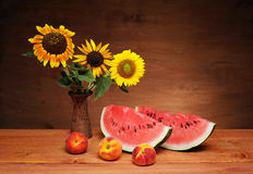 Sunflowers in a vase and watermelon Royalty Free Stock Images