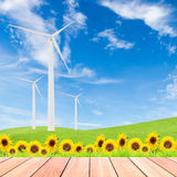 Sunflowers with wind turbine on green grass field against blue s Royalty Free Stock Photo