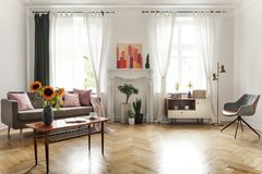 Sunflowers on wooden table next to sofa in spacious flat interior with armchair and poster. Real photo. Concept stock image