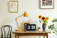 Sunflowers, yellow lamp and laptop on wooden desk in home office interior with posters. Real photo