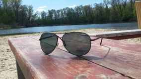 Sunglases on the background of the river. Sunglases on the background royalty free stock photos