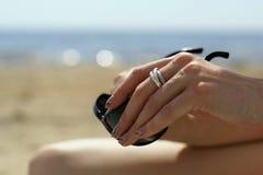 Sunglases en una mano de la muchacha Fotografía de archivo libre de regalías