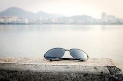 Sunglass和湖旁边城市背景 图库摄影